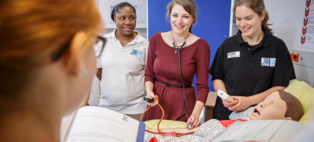 Studentinnen üben die Behandlung eines Patienten an einer Übungspuppe.
