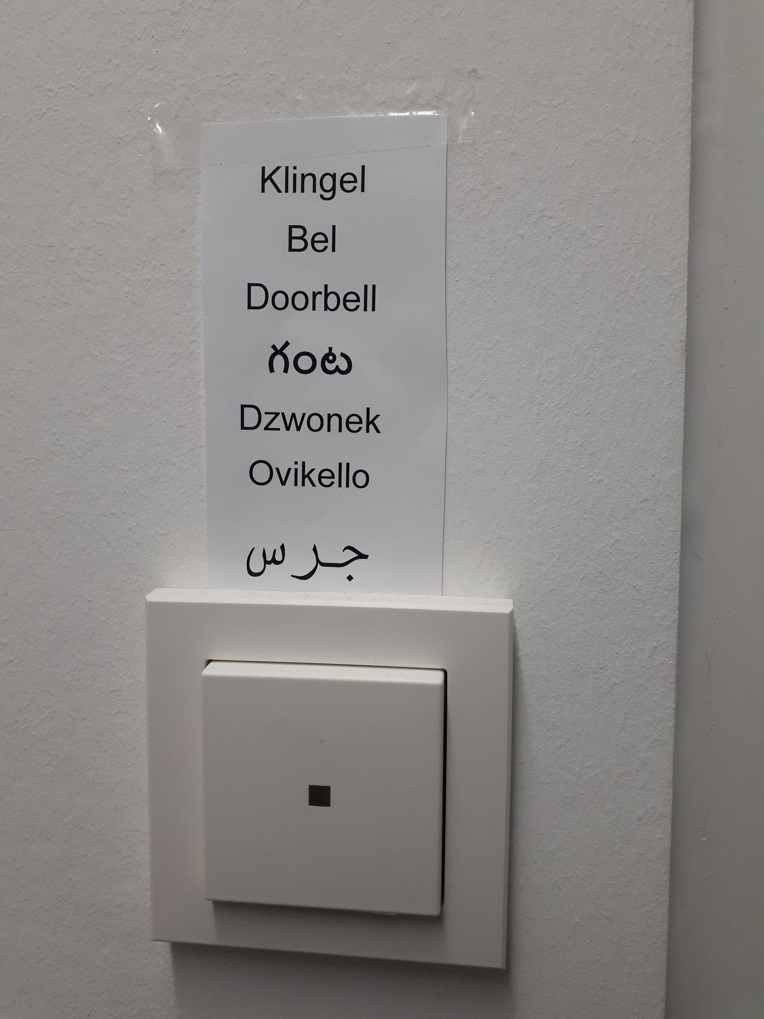 Abgebildet ist eine Türschelle, die mit dem Wort Klingel in sieben verschiedenen Sprachen beschriftet wurde.