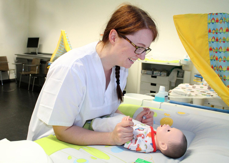 Christina Malow übt den Umgang mit besonders kleinen Patient*innen im 'Kinderpflegezimmer' tranieren, einem von vielen Skills-Labs an der Hochschule.