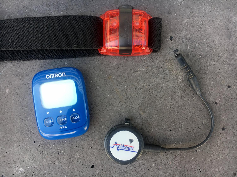 Das rote Gerät ist ein dreidimensionaler Akzelerometer (ActiGraph), das schwarze Gerät mit dem Kabel ist ein kombiniertes Gerät zur Erfassung der Herzfrequenz und Beschleunigung (Actiheart) und das blaue Gerät ist ein einfacher, handelsüblicher Schrittzähler.