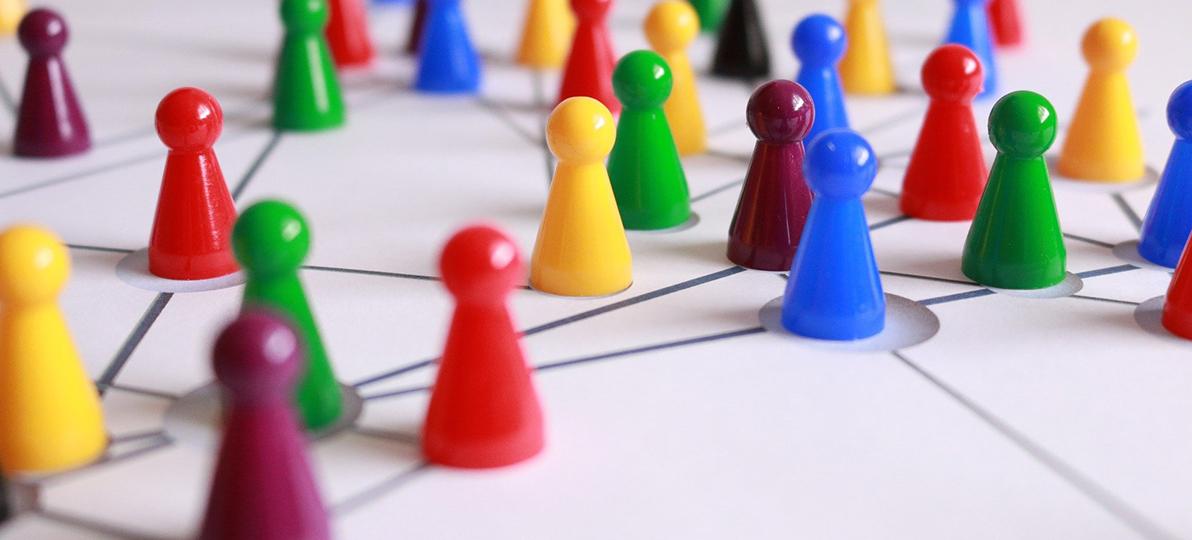 Zu sehen sind Spielfiguren, die mit Linien verbunden sind. Es ist ein Symbolbild für Netzwerkarbeit.