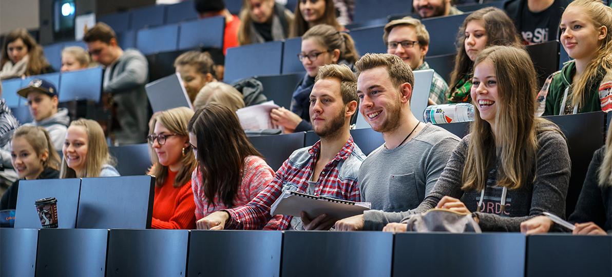 Das Bild zeigt Studierende, die in einem Hörsaal sitzen.