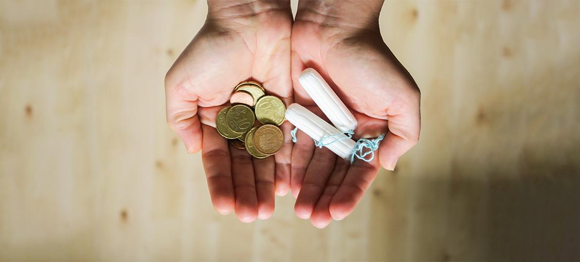 Zu sehen sind zwei Hände, von denen die eine Geld und die andere zwei Tampons hält.